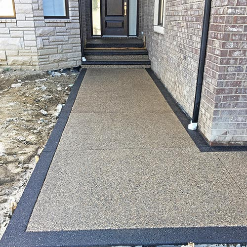 Exposed aggregate front walkway with stained borders